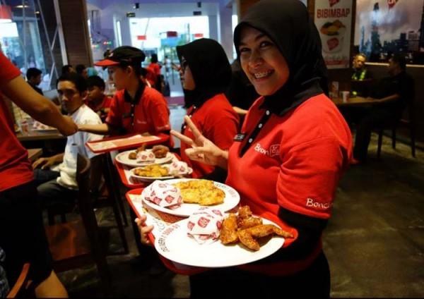 Para pegawai sedang mempersiapkan layanan berbagai produk dari BonChon Chicken yang akan diberikan ke pelanggan