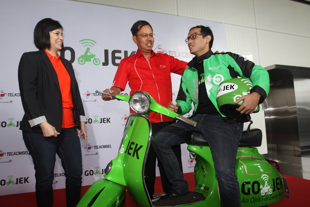 Direktur Sales Telkomsel Mas'ud Khamid (paling tengah), Presiden Direktur Tiphone Mobile Indonesia Tan Lie Pin (paling kiri) dan CEO GO-JEK Nadiem Makarim (paling kanan) saat melakukan kerjasama hari ini Senin (15/2) di Jakarta.