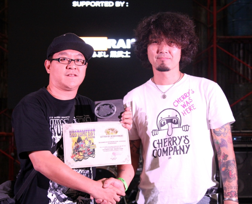 Juri dari Cherry's Company Kaiciroh Kurosuh menyerahkan penghargaan runner up kategori Kustom Bike Show Nitro Head FFA Free For All kepada pemenang Charles R Wawolangi yang juga pemenang HMC 2016 pada ajang Kustomfest 2016 yang diselenggarakan di Jogja Expo Center (JEC), Yogyakarta.  Ist