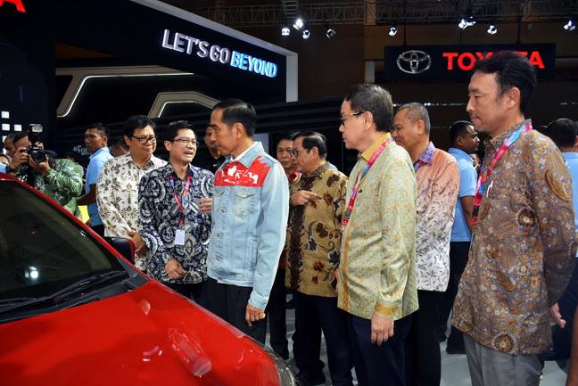 Presiden Joko Widodo didamping Menteri Perindustian Airlangga Hartarto (kiri) dan Menteri Sekretariat Kabinet Pramono Anung (keempat kanan) tengah mendengar penjelasan tentang Sedan Vios terbaru produk Toyota dari Wakil Presiden TAM Henry Tanoto (kedua kiri) disaksikan Presiden Direktur PT Astra International Prijono Sugiarto (tiga kanan) dan Presiden Direktur TAM Yoshihiro Nakata (kanan), saat mengunjungi booth  Toyota pada pembukaan Indonesia International Motor Show (IIMS) 2018, di JIExpo Kemayoran, Kamis (19/4).   Ist