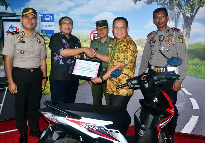Ketua YAHM I Putu Astawa menyerahkan bantuan kepada Ketua Yayasan Mitra Industri MM2100 Darwoto berupa sepeda motor dan HRT sebagai alat peraga keselamatan berkendara dalam Laboratorium Safety Riding SMK Mitra Industri MM2100.  Ist
