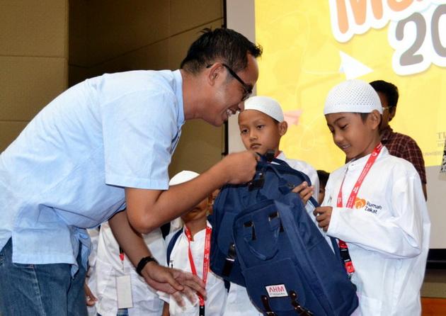 Deputy Head of Corporate Communication AHM Ahmad Muhibbuddin memberikan bingkisan berupa peralatan sekolah dan perlengkapan ibadah kepada peserta khitanan massal DKM AHM. Ist
