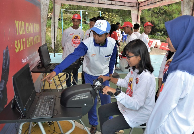 Instruktur Safety Riding Honda menjelaskan penggunaan Honda Riding Trainer (HRT) kepada salah satu peserta Student Camp. HRT merupakan alat simulasi berkendara sepeda motor yang mampu menampilkan beragam kondisi jalan dan suasana.  Ist